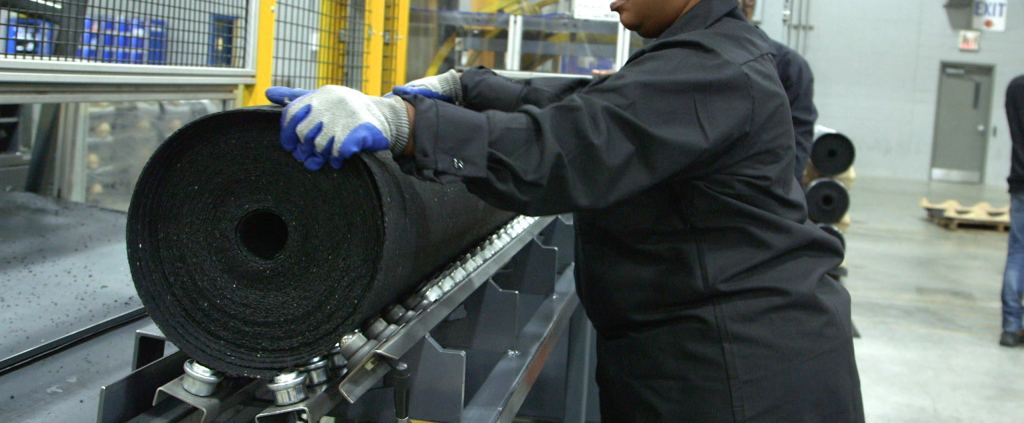 Operator at Pliteq factory rolling a GenieMat RST roll